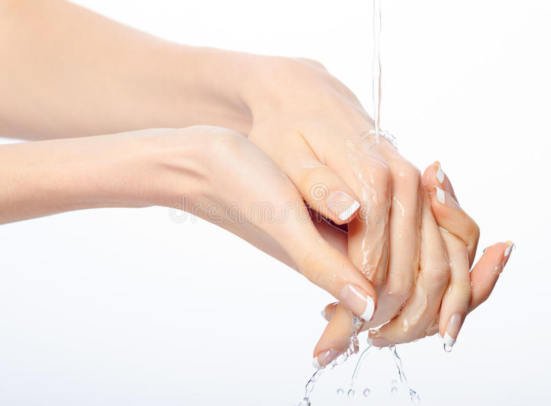 Female hands with french manicure washed in clear fresh water stock photo