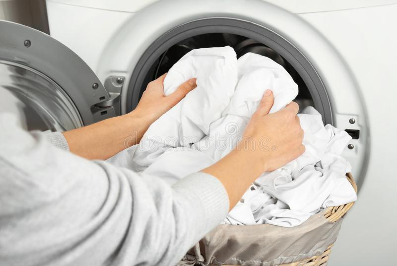 Female hands getting out clean clothes. From washing machine stock photos