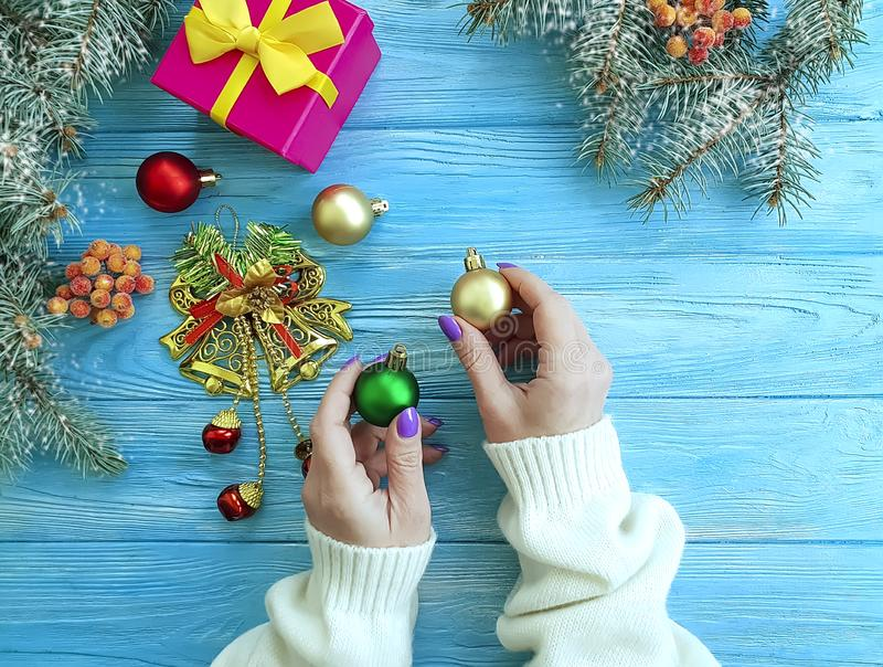 Female hands gift box, ball, border present decoration seasons Christmas tree branch on a wooden background. Female hands gift box, ball Christmas tree branch on stock photography