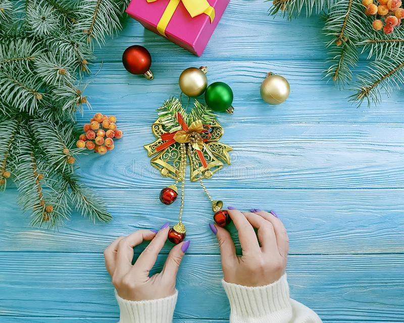 Female hands gift box, ball, border holiday present decoration seasons Christmas tree branch on a wooden background. Female hands gift box, ball Christmas tree royalty free stock photo