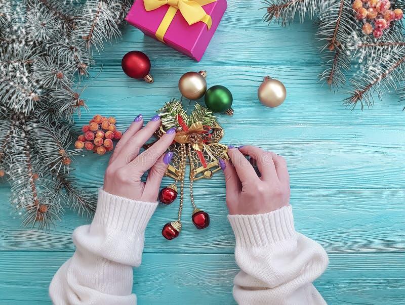 Female hands gift box, ball, table border holiday present decoration seasons Christmas tree branch on a wooden background. Female hands gift box, ball Christmas stock image