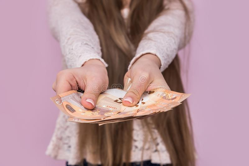 Female hands giving euro banknotes on pink royalty free stock image