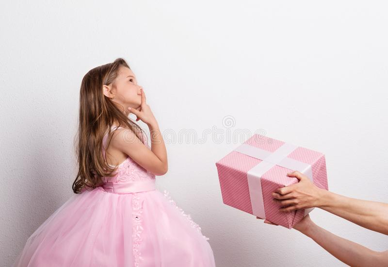 Female hands giving a present to a small girl dressed in princess dress. Studio shot. stock photo