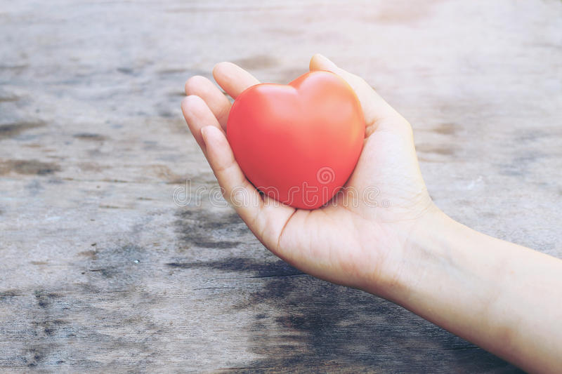 Female hands giving red heart overhead of wooden planks in the morning light. Filtered color. vintage tone. royalty free stock photography