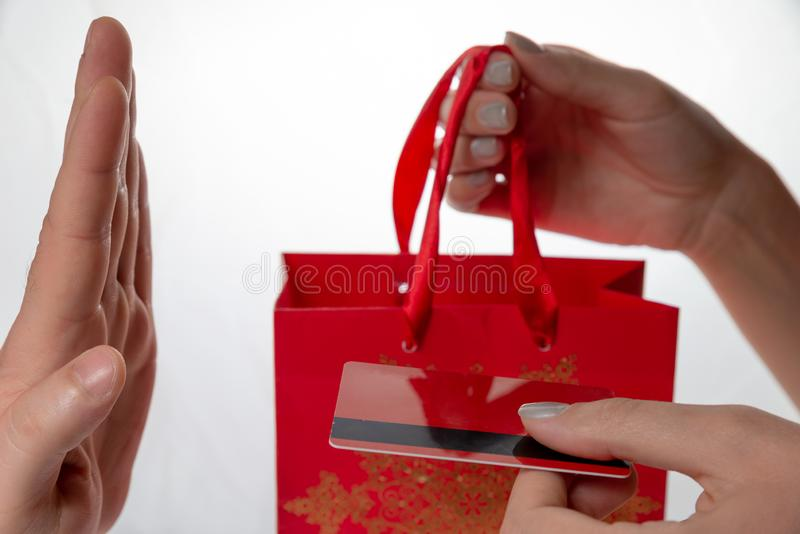 Female hands are giving the red package and red credit card with black line to man hand. Man hand are refusing. On the white backg royalty free stock photos