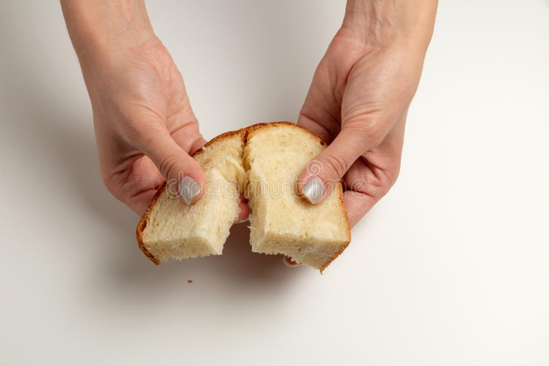 Female hands are giving the two pieces of the white bread on the white background/table. International Day to Assist the Poor royalty free stock photography