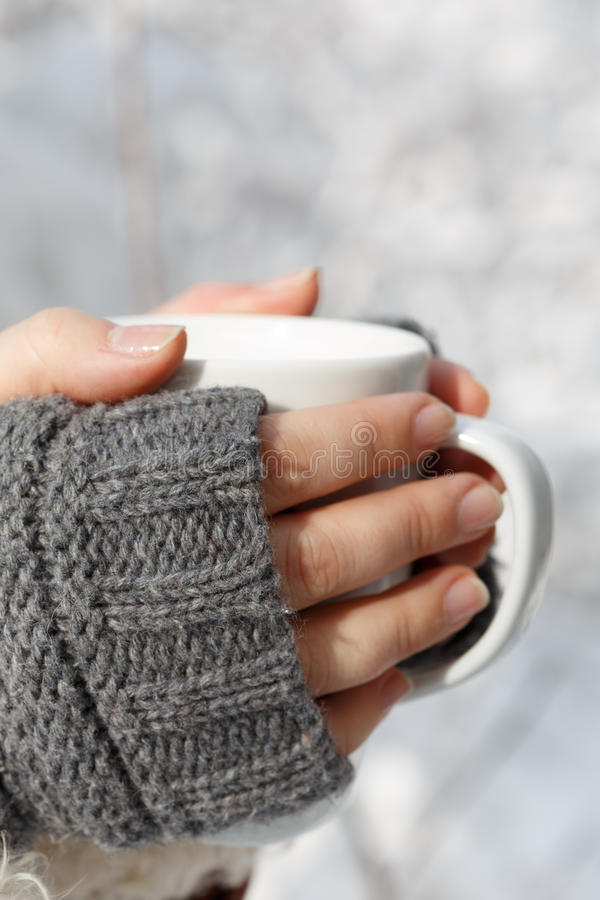 Female hands in gray fingerless mittens with white cup of tea in. Women's hands in gray fingerless knitted mittens holding white cup of tea at the background of stock image