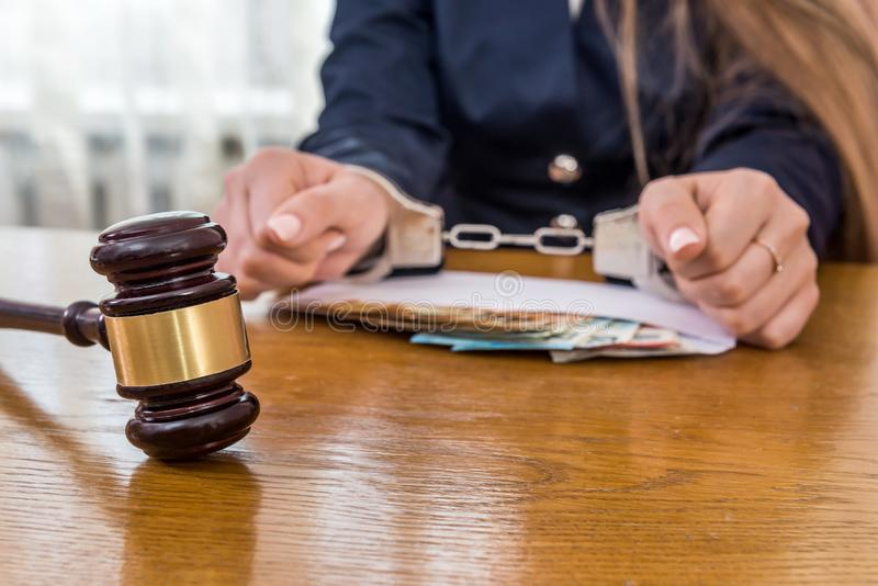 Female hands in handcuffs with money and gavel royalty free stock images