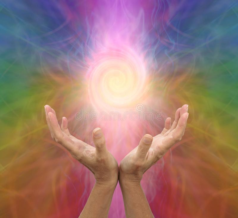 Channelling rainbow coloured  vortex healing energy. Female hands held open and palms upwards with a spiralling energy formation above on a multicoloured stock photos