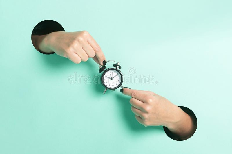 Female hands hold alarm clock through a hole on neon mint background. Minimalistic creative concept. stock images