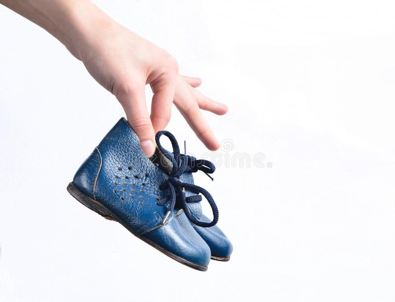 Female hands hold children& x27;s leather boots on a white background. Female hands hold children& x27;s leather boots on a white background stock image