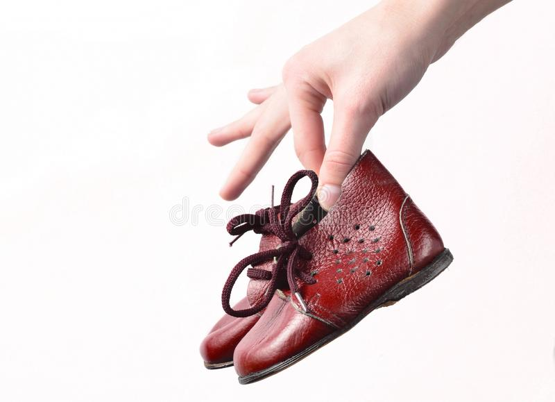 Female hands hold children& x27;s leather boots on a white background. Female hands hold children& x27;s leather boots on a white background royalty free stock image
