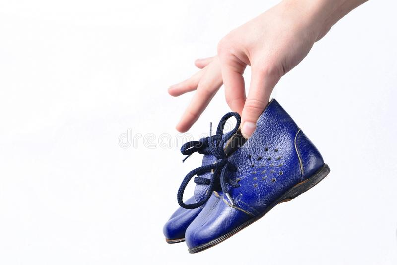Female hands hold children& x27;s leather boots on a white background. Female hands hold children& x27;s leather boots on a white background royalty free stock images