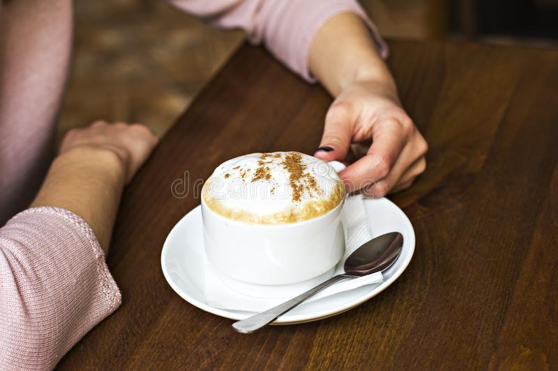Female hands hold a cup of cappuccino in a cafe. royalty free stock photo