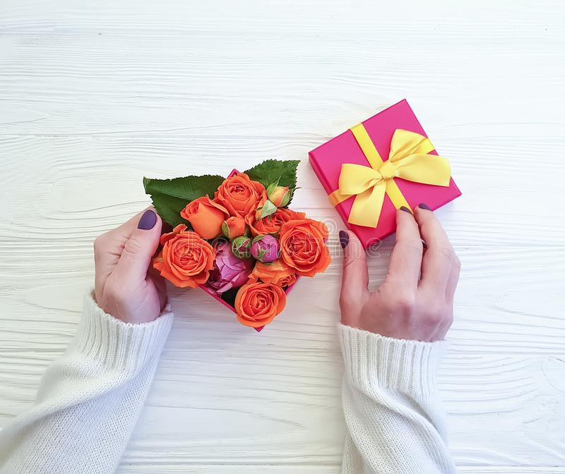 Female hands hold gift box, surprise romance rose flower congratulation on wooden background stock photos