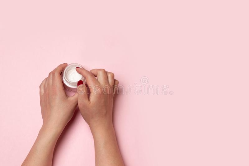 Beauty treatments. Female hands hold a glass jar with a cream or skincare cosmetic and smear their hands royalty free stock image