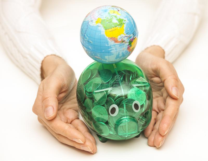 Female hands hold the Globe and piggy bank. Global finance concept stock photography