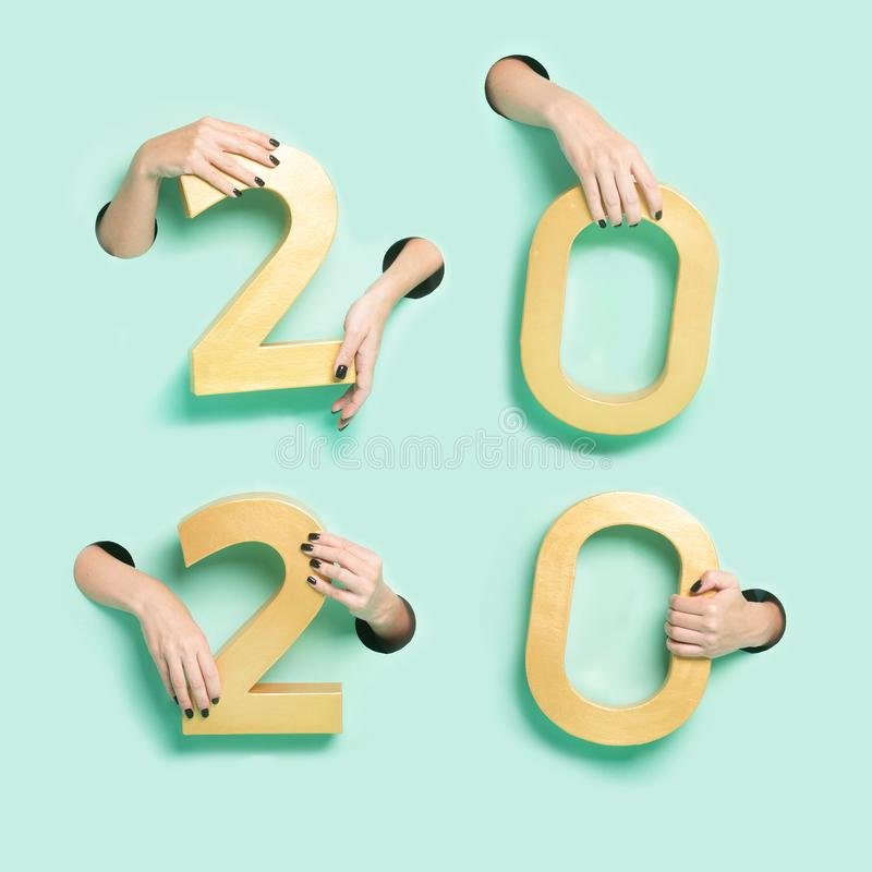 Female hands hold golden new year 2020 digits through a hole on neon mint background. Minimalistic creative xmas stock image