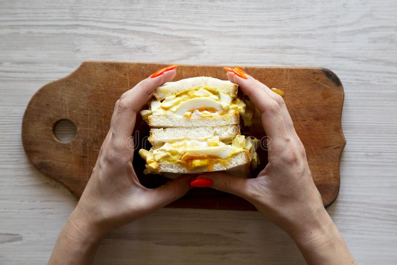Female hands hold homemade egg salad sandwich, top view. Overhead, from above stock image