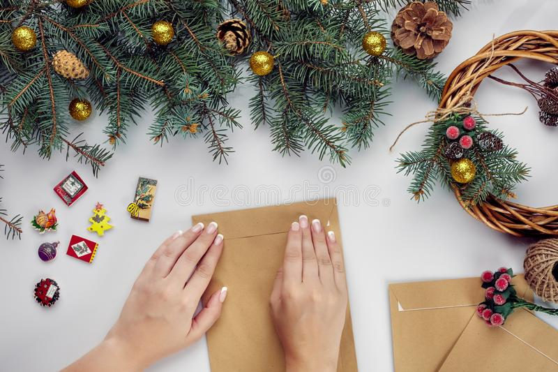 Female hands hold Merry Christmas card and envelope. Christmas decoration background. Flat lay, top view. royalty free stock photography