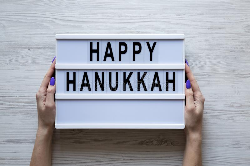 Female hands hold modern board with text `Happy Hanukkah` over white wooden background, overhead view. From above, flat lay stock images