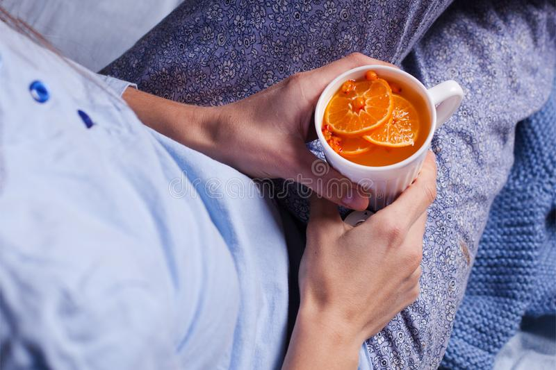 Female hands hold a mug of hot tea of orange color - tea with mandarins of sea-buckthorn, prevention of cold and flu in the cold stock photos