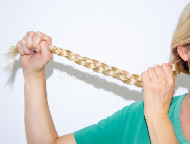 Female hands hold a pigtail stock images