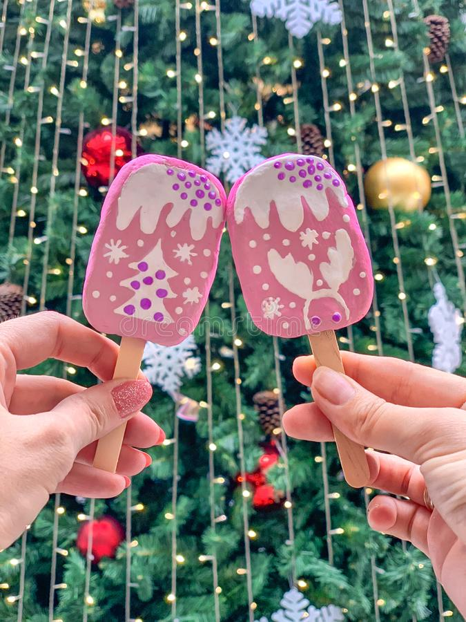 Female hands hold pink ice cream on a stick, against the background of the Christmas tree royalty free stock images