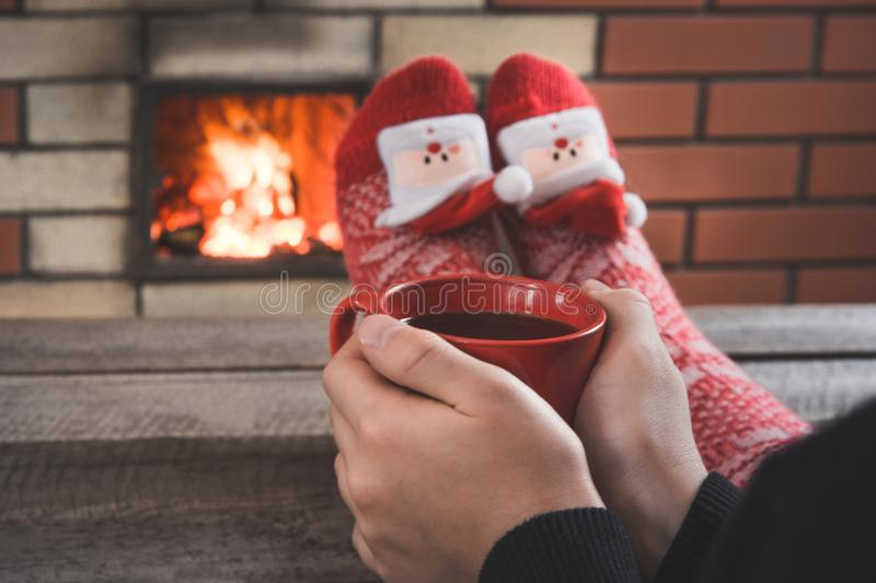 Red cup of coffee in female hand by the fireplace. Female relaxes by warmfire in christmas red socks. Christmas holiday. royalty free stock photos