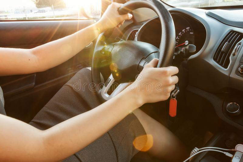 Female hands hold the steering wheel, close-up. A woman is driving a car. Toned. royalty free stock photography
