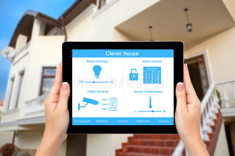 Female hands hold a tablet with system clever house on the background of the house. Female hands hold a tablet computer with system clever house on a screen on royalty free stock photo