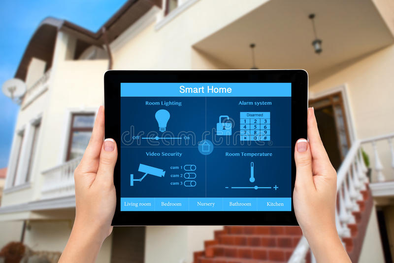 Female hands hold a tablet with system smart house on the background of the house. Female hands hold a tablet computer with system smart house on a screen on the royalty free stock photos