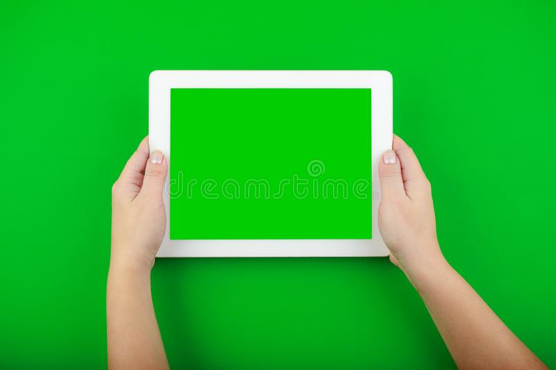 Female hands hold a white tablet with a blank screen stock image