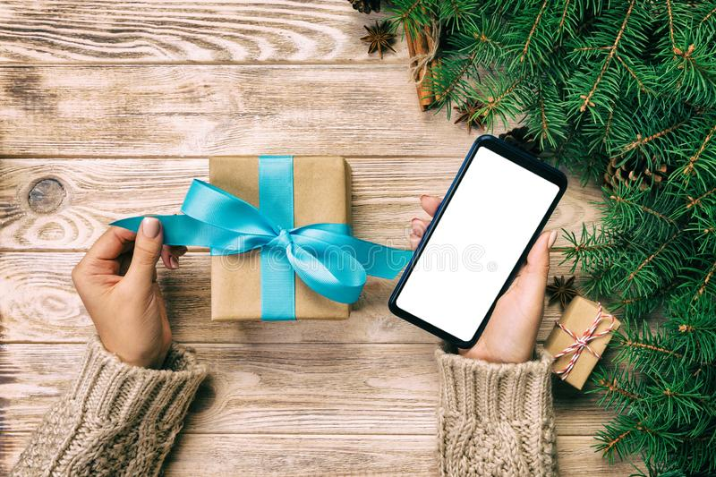 Female hands hold wrapping christmas gift box and reading massage on phone with blue ribbon on brown wooden vintage table. Top vie royalty free stock photos