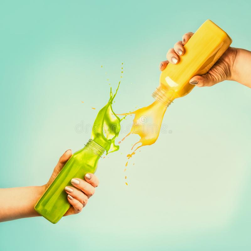 Female hands holding bottles with yellow and green splash smoothie or juice on blue background with tropical leaves and fruits. Summer beverages concept stock photos