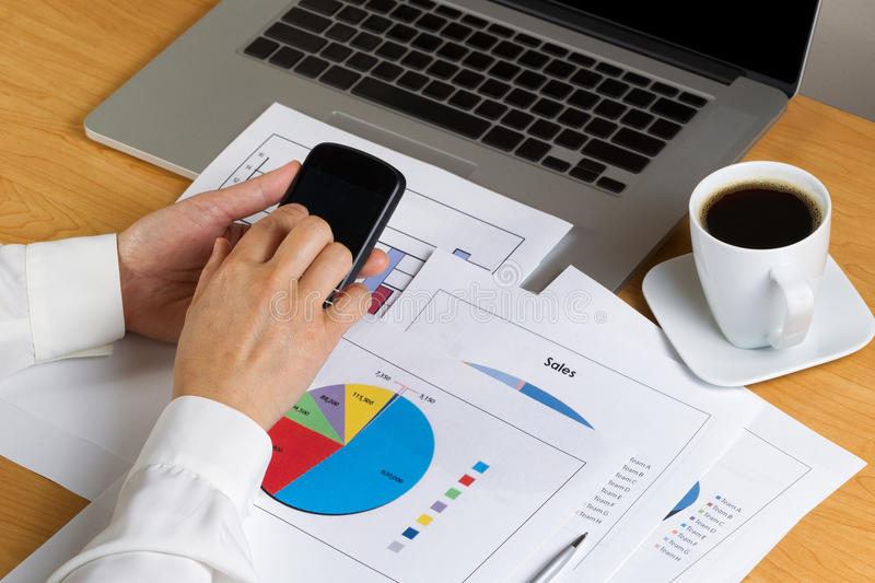 Female hands holding cell phone while looking at financial chart stock photos