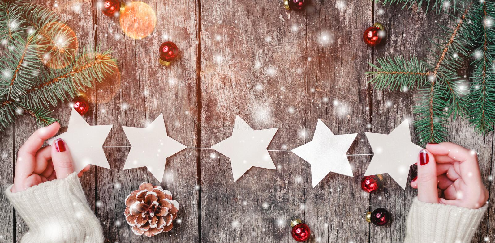 Female hands holding Christmas garland of stars on wooden background with Christmas gifts, Fir branches, red decorations. stock images