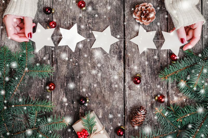 Female hands holding Christmas garland of stars on wooden background with Christmas gifts, Fir branches royalty free stock images