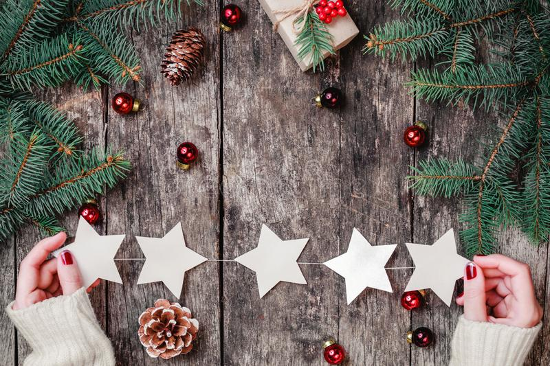 Female hands holding Christmas garland of stars on wooden background with Christmas gifts, Fir branches stock photos
