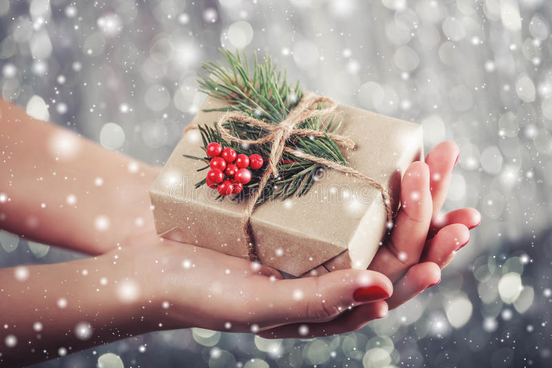 Female hands holding Christmas gift box with branch of fir tree, shiny xmas background. Holiday gift and decoration stock photos