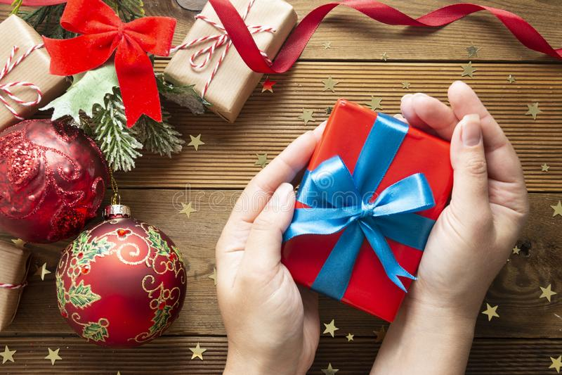 Female hands holding Christmas present, red gift box. Packaging wrapped gift box on wooden background. Christmas winter stock photo