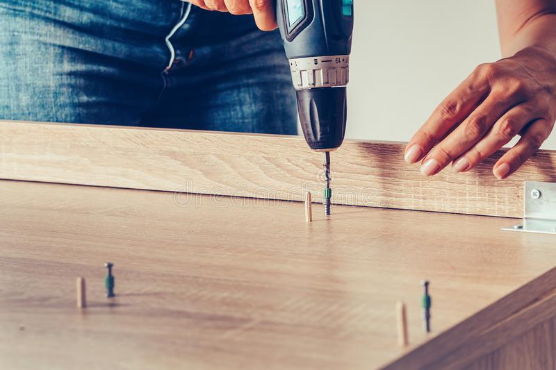 Female hands holding a cordless drill assembling  furniture royalty free stock photography