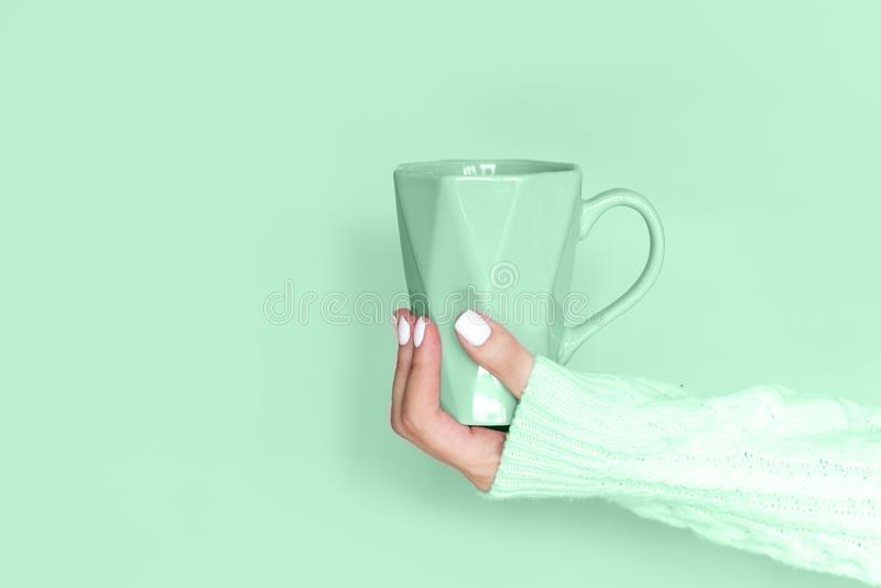 Famale hands holding a cozy ceramic handmade mug with coffe. Winter and Christmas home time concept. Lifestyle. Copy space. Female hands holding a cozy ceramic royalty free stock photography