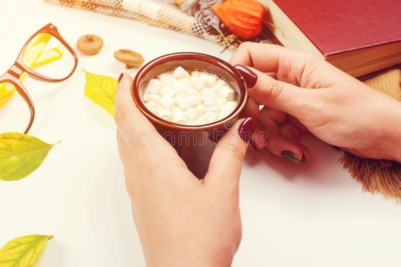 Female hands holding cup of cacao. Autumn table with leaves, book, glasses and coffee. Autumn mood. Mockup royalty free stock photo