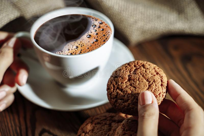 Female hands holding cup of coffee and cookie on wooden table close up stock images