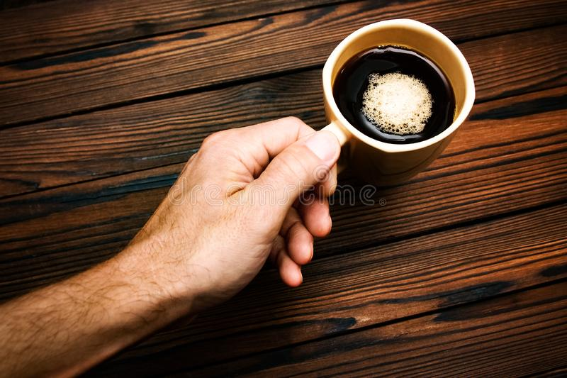 Female hands holding cup of coffee on wooden background. A Female hands holding cup of coffee on wooden background stock images