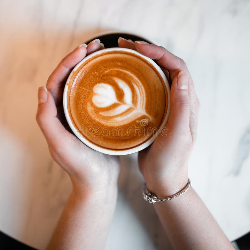 Female hands holding a cup with a delicious latte on the background of a vintage table. Morning coffee break in a cafe. Close-up. View from above royalty free stock photography