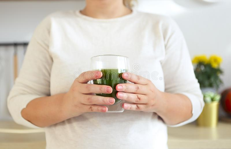 Female hands holding cup of green matcha tea closeup stock images