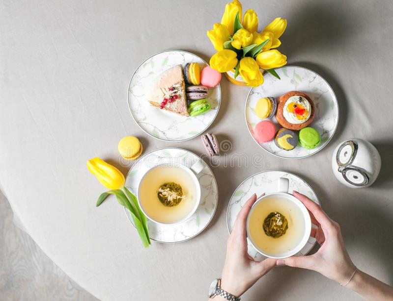 Female hands holding cup of green tea. top view. Beautiful morning in home. A lot of cake and desserts. Copy space stock image