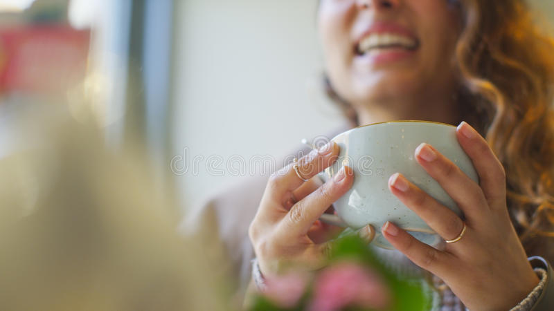 Female hands holding a cup of hot drink in a cafe stock photo